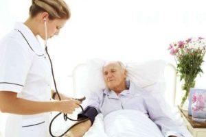 измеряет давление лежачему больному
